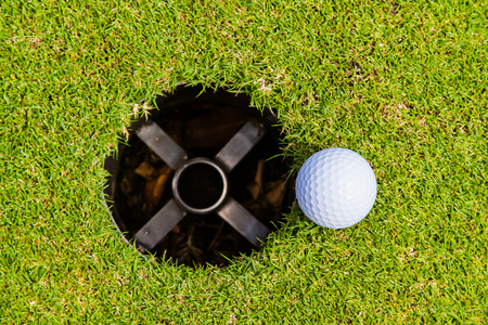 Golf ball in the grass is a sport that is popular worldwide.