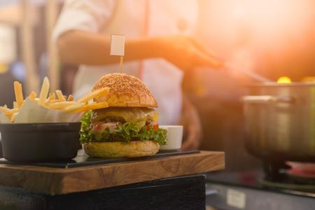 Der Chef ist gebraten Pommes frites und hat ein Hamburger Gericht Lizenzfreie Bilder