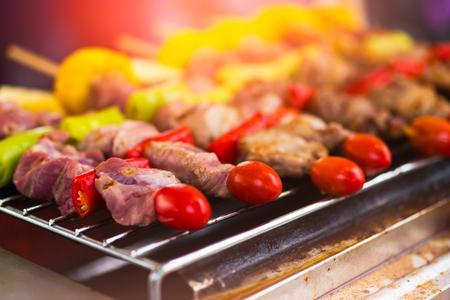 Ein köstlicher Grill mit Schweinefleisch, Huhn, Tomaten, Chili, Mais und mit Sauce