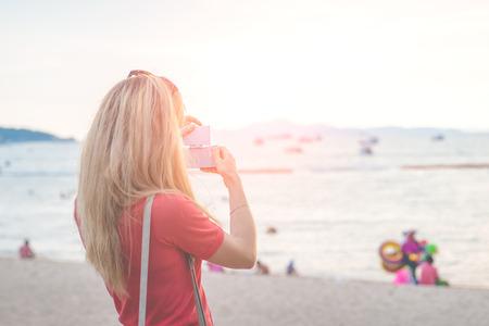 Frau, die ein Foto am Strand nimmt Lizenzfreie Bilder