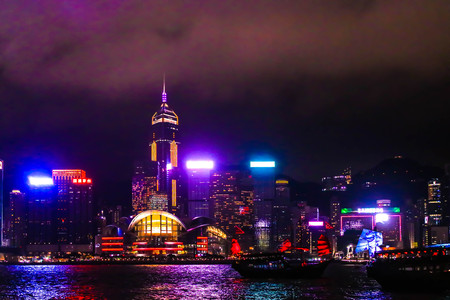 Landscape of Symphony of Lights and two boat of life at Victoria Harbor in Hong kong Editorial