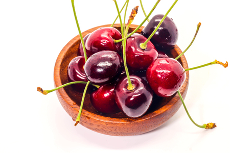 Close up of group Fresh cherry on dark brown wooden cup