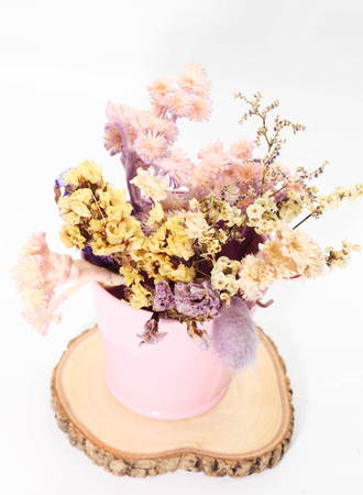 Close up of bouquet of dried many flower on pink bucket and round teak wood