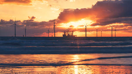 Sunrise on Redcar beach looking at the offshore North Sea wind farm