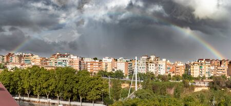 Stunning rainbow appearing through the clouds after a thunderstorm in a city. Image taken in Esplugues de Llobregat, Spain.