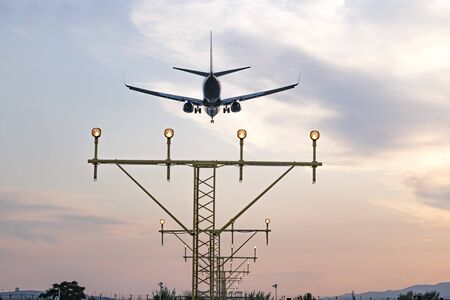 Aircraft during the approach procedure at sunset overflying the runway lights