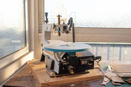 Wood cutting band saw in a workshop with sawdust