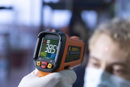 Laser infrared thermometer temperature control to an unidentifiable person showing high fever over 38 celsius degree 스톡 콘텐츠