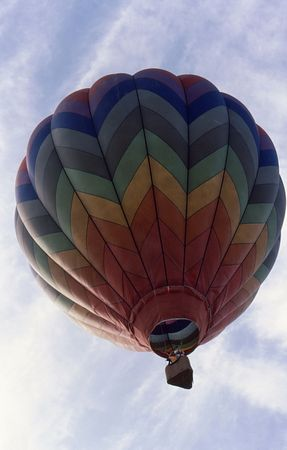 brightly colored hot air Balloon ascending into a coludy sky