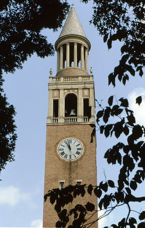 Old clock tower and steeple framed by trees