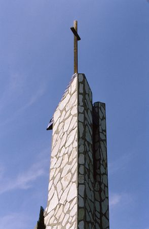 Church tower of unusual design and shape with cross