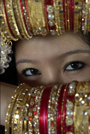 young shy woman hiding her face with her bangle covered arms. only eyes visible Stock Photo
