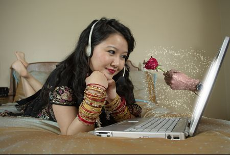 girl lying on bed wearing a sari, talking online to a friend, imagining him giving her a flower