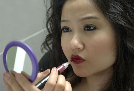 woman applying lipstick while looking in mirror