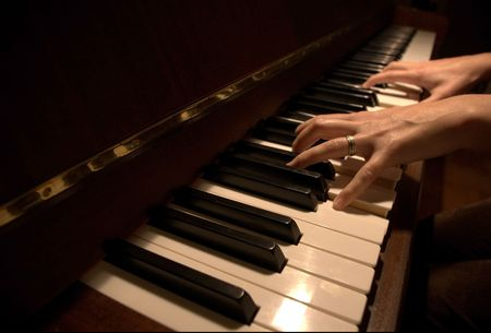 piano closeup: a pair of womans hands playing a petrof piano. Stock Photo