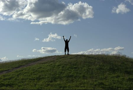 man standing on top of grassy hill victorious with hands up in the air cloudy sky in background Stock Photo