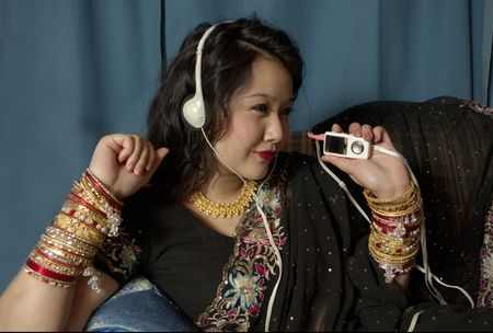 indian girl wearing sari laying on couch listening to music on her MP3 player