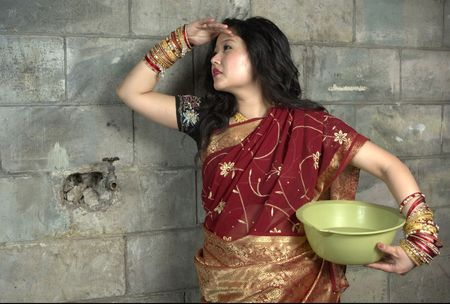 indian woman with long black hair in red and gold sari looking into the distance. Background is a dirty cement block wall