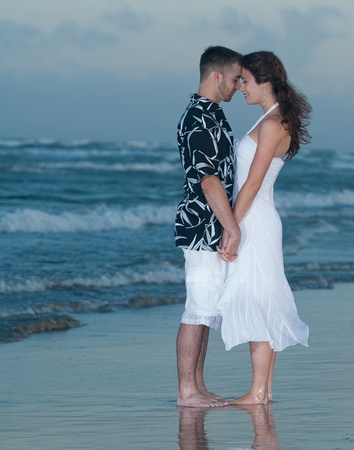 Engaged couple holding hands on beach photo