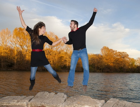 Couple holding hands jumping in air by river at autumn photo