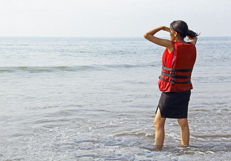 life jacket: Teen girl in life jacket waiting at the beach