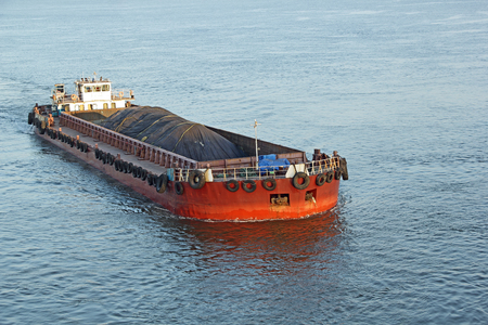 transported: Iron ore mined in hinterland transported to the main harbor in large cargo boat for loading into big ships for exporting in India