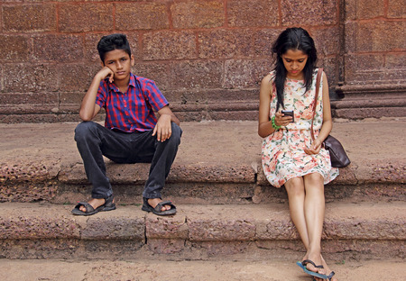 communication breakdown: Teen girl and boy sitting in brick steps. Boy unhappy with girl friend�s obsession for mobile phone. Shows breakdown of face-to-face communication of present times.