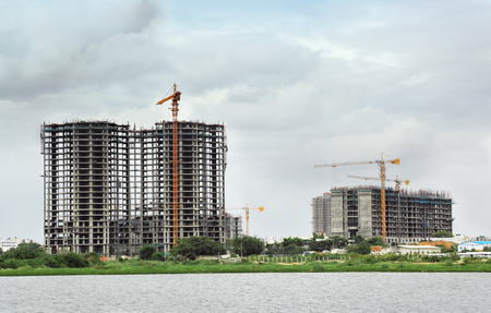 la construcción de edificios de gran altura mediante grúas torre y otros equipos de construcción Foto de archivo