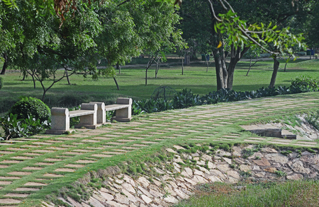 paved: Two stone park benches along a pathway paved with rough granite stone tiles Stock Photo