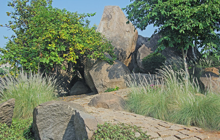 winding up: Winding pathway paved by rough granite stone tiles, going up through hilly terrain with huge boulders and bushes.