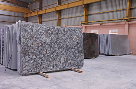 Various shades of Indian polished natural granite floor slabs kept in stacks in storehouse Foto de archivo