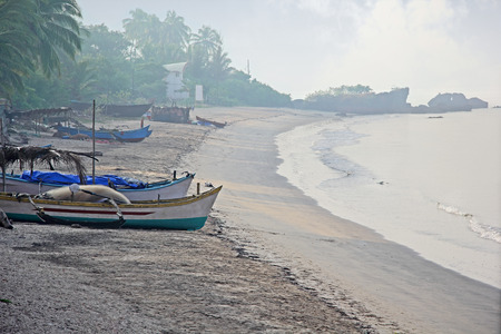 fishing scene: Morning scene of fishing boats resting on the beach at Siridao fishing village in Goa, India