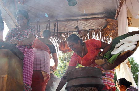 enact: Goa, India - August 27, 2016: Village women enact the old style village kitchen chores in a float during the Bonderam 2016, the 33rd Traditional Flag Festival of Divar Island in Goa, India. For editorial use only