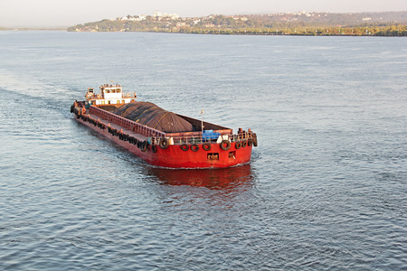 Large cargo boat transporting iron ore mined in hinterland to the main harbor for loading into big ships for exporting in India