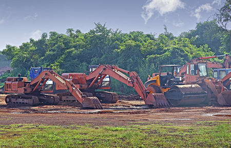 Heavy construction and earthmoving hydraulic equipment parked after work at project site