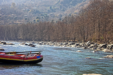 Anchored white water rafting boat in the Himalayas at the Beas river in Manali, India.