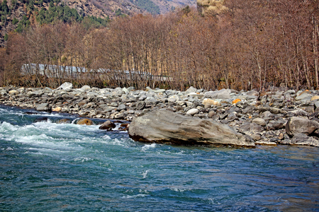Beas river forming rapids while flowing through granite boulders at the Manali region of the Himalayas. White water rafting is a popular sport here.
