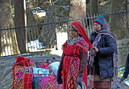 local 27: Manali, India - December 27, 2013: Local woman of Manali dressing a tourist in the traditional tribal attire, pattoo, of Kullu valley in the Himalayan mountain ranges of India