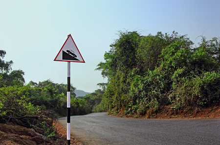 Road signage board alerting motorists to be careful at the steep slope ahead in a highway through forest in hilly area
