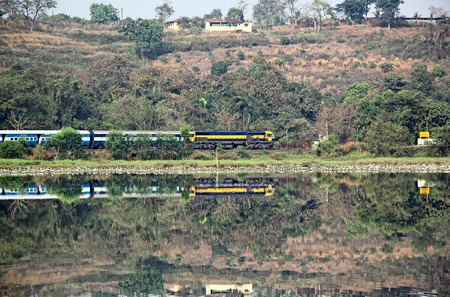 Passenger train of Indian Railways passing along the banks of lake in a hilly terrain, approaching a station in Goa, India
