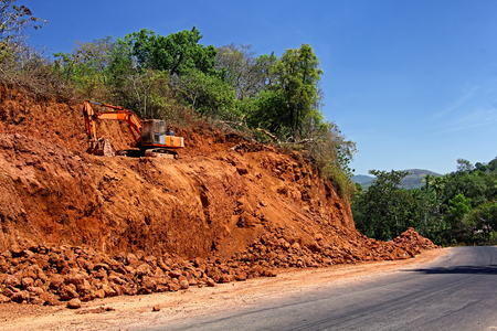 Massive earth cutting using heavy construction and earthmoving hydraulic equipment being done for widening highway in a hilly terrain