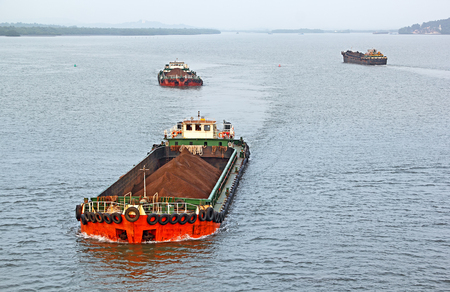 Large cargo barges transporting iron ore mined in hinterland to the main harbor for loading into big ships for exporting, along Mandovi River in Goa, India