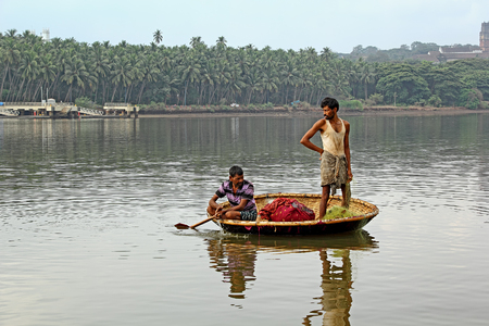 circular blue water ripple: Goa, India - April 16, 2017: Local fishermen in circular boat harvest the fish hooked in trap net laid the previous night for catching fish in the Mondovi River in Old Goa, India