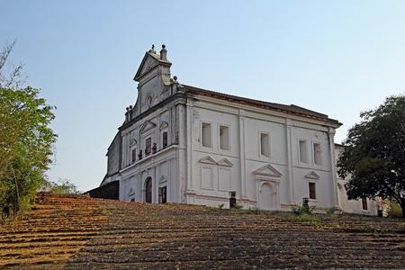 Capilla de Nuestra Señora del Monte con la escalera de la rampa en piedras de laterita en Monte Hill en Old Goa, India. Todos los meses de febrero se celebra aquí el Monte Music Festival. Foto de archivo - 77003622
