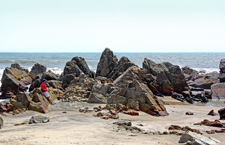 Lone tourist appreciating the rocky, spiky, rugged and sculpture type shoreline of Arambol beach in Goa, India Stock Photo
