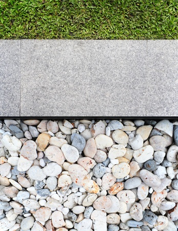 Grass, tiles and stones in the decorative garden photo