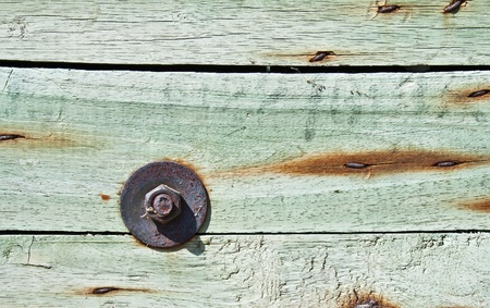 Closeup shot of rusty screw with wooden wall photo