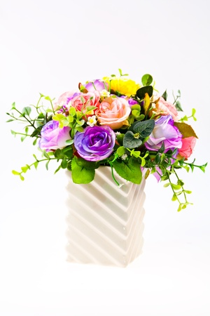 Colorful artificial beautiful flowers in a vase isolated on white background