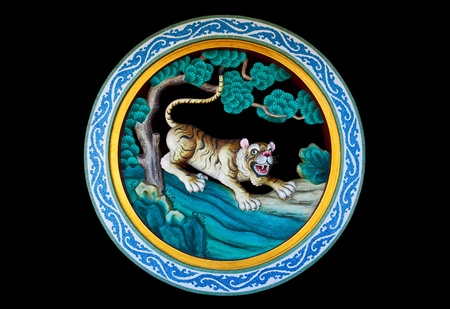 Tiger in a forest statue on a Chinese temple wall isolated on black background photo