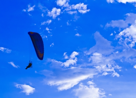 Conceptual image of paramotor silhouette in blue sky photo